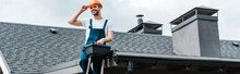 Panoramic Shot Of Happy Repairman Sitting On Roof And Holding Toolbox
