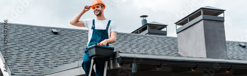 Fotografiet panoramic shot of happy repairman sitting on roof and holding toolbox