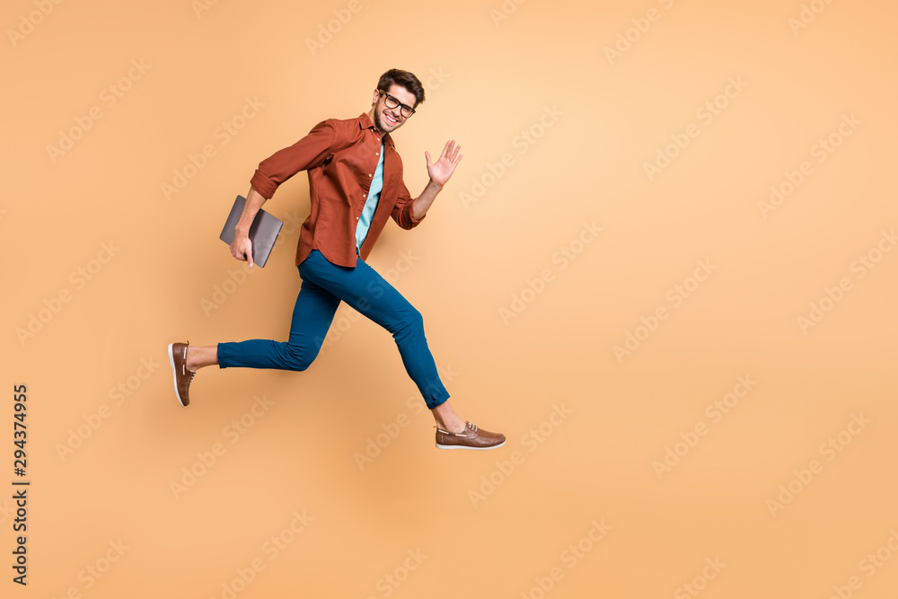 Fototapety, obrazy: Full length body size view of his he nice attractive cheerful cheery glad content guy jumping in air carrying laptop running fast late hurry-up meeting isolated over beige color pastel background