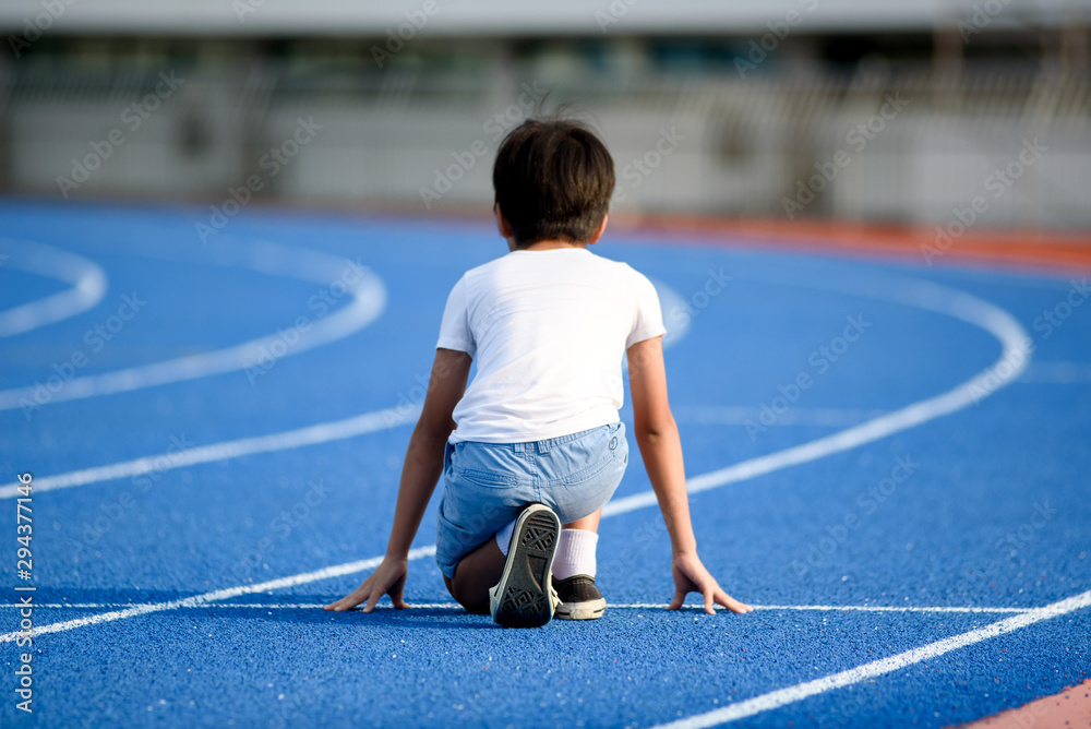 Fototapety, obrazy: Young boy running on blue track