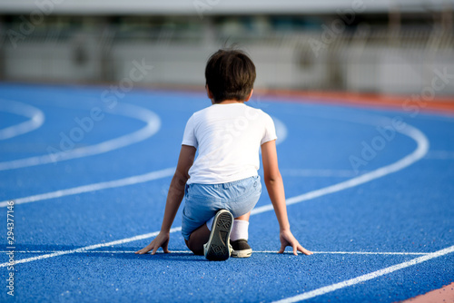 Young boy running on blue track
