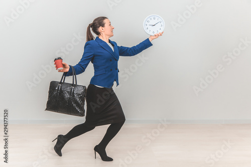 Fototapeta Young teacher in formal suit with bag, holding a white clock, cup of coffee, hurrying up. obraz