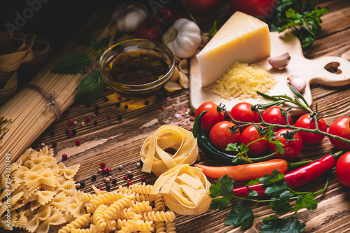 Canvas-taulu Tasty appetizing italian spaghetti pasta ingredients for kitchen cuisine with tomato, cheese parmesan, olive oil, fettuccine and basil on wooden brown table