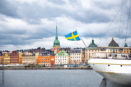 Foto auf Gartenposter Stockholm Swedish flag on the boat against Stockholm old city. Panoramic view of Gamla Stan from Baltic Sea, Sweden.