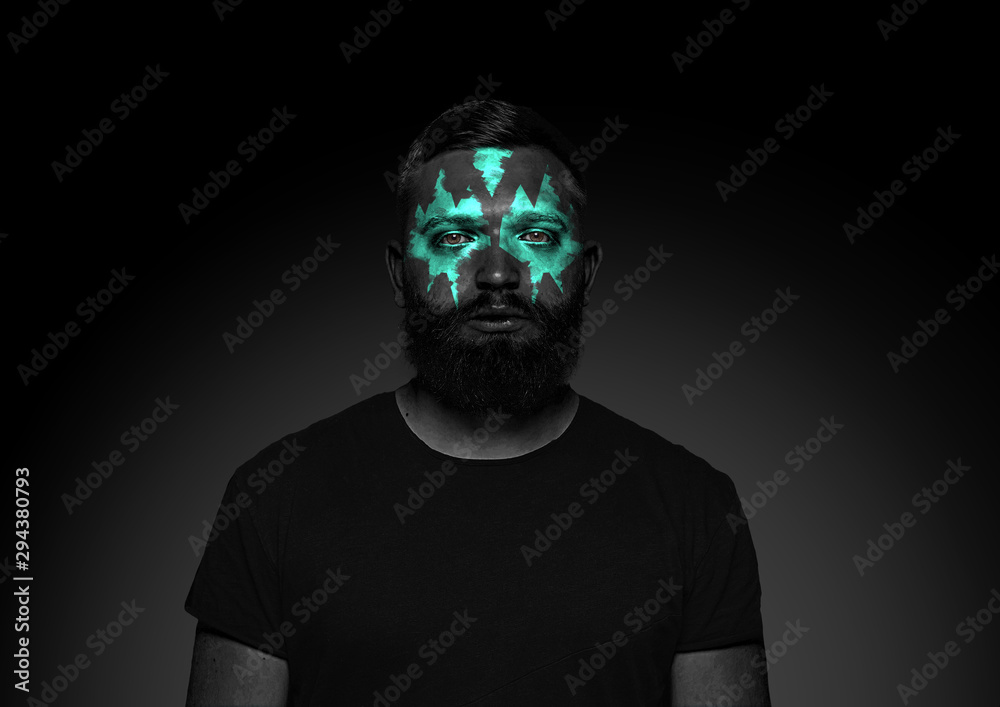 Fototapeta Discover what's inside you. Close up portrait of young man isolated on black studio background. Bright neon light on the face. Halloween, scary look theme, october holidays, horror concept.