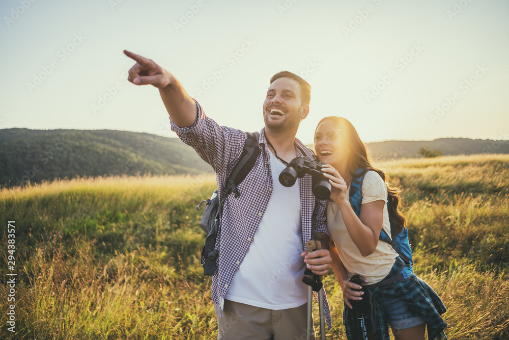 Fototapety, obrazy: Happy couple is hiking in mountain. They are watching nature with binoculars.
