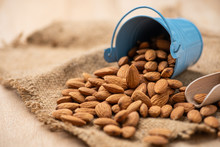 Almonds Pour From Blue Bucket. On Wooden Table. Almond Concept With Copyspace.