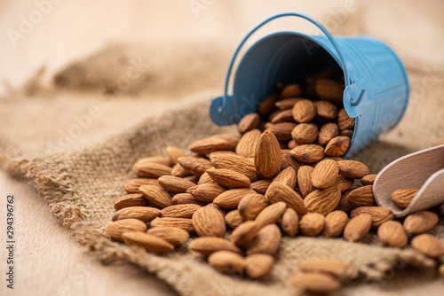 Almonds pour from blue bucket Wallpaper Mural
