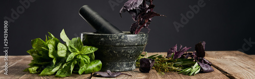 Fotografija panoramic shot of mortar and pestle with basil on wooden table isolated on black