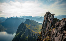 Adventurous Man Is Standing On Top Of The Mountain And Enjoying The Beautiful View During A Vibrant Sunset. Taken On Top Senja, Norway