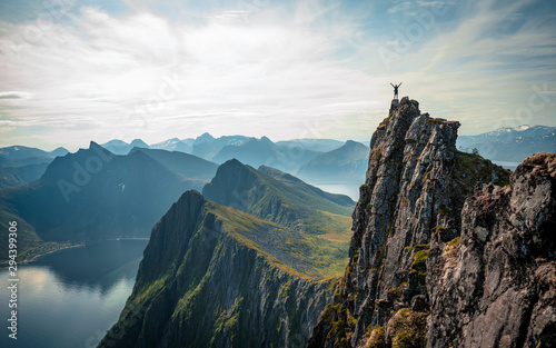 Foto auf Gartenposter Weiß Adventurous man is standing on top of the mountain and enjoying the beautiful view during a vibrant sunset. Taken on top Senja, Norway