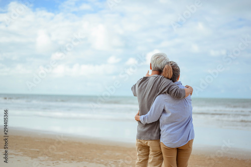 Fototapeta A senior couple hugged each other at the beach in the morning