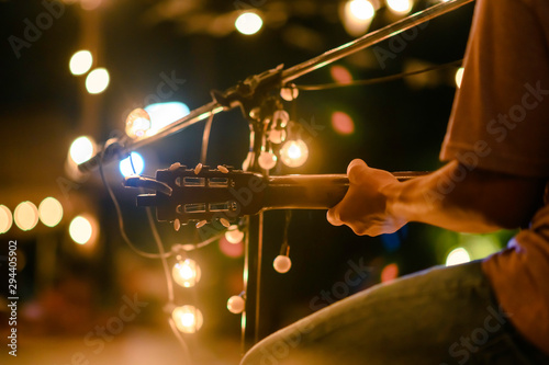 Rear view of the man sitting play acoustic guitar on the outdoor concert with a microphone stand in the front, musical concept. - 294405902