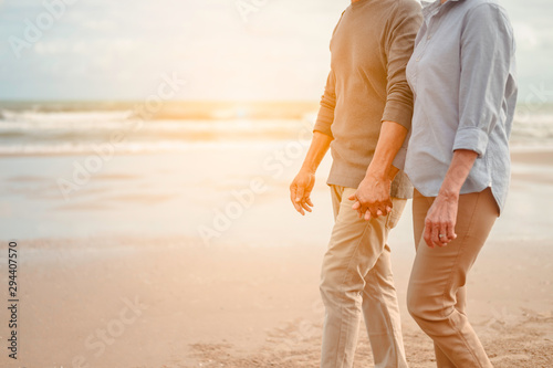 Fotomural  Senior lovers walk hand in hand at the beach at sunset, plan life insurance at retirement concept