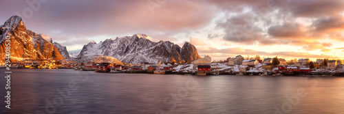 Foto auf AluDibond Lachs Scenic view of Reine, famous fishing village at sunrise, Lofoten Islands, Norway. Amazing winter landscape with rocky mountains, traditional rorbues, water and dramatic cloudy sky, travel background