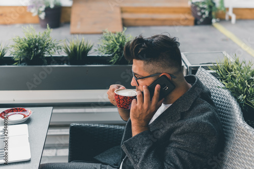 Young beard man using laptop on office, freelance work, outdoor close up hipster portrait, brutal, guy listening music on earphones, make photo and video, production, Bali, watch OS - 294409517