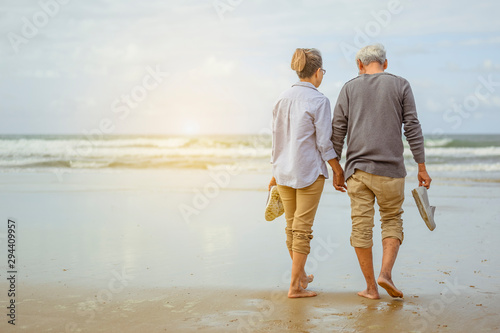 Senior couple walking on the beach holding hands at sunrise, plan life insurance at retirement concept. - 294409957