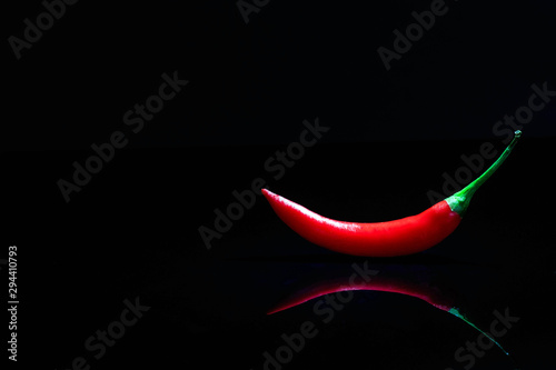 Printed kitchen splashbacks Hot chili peppers Red chili on black acrylic glass with reflection