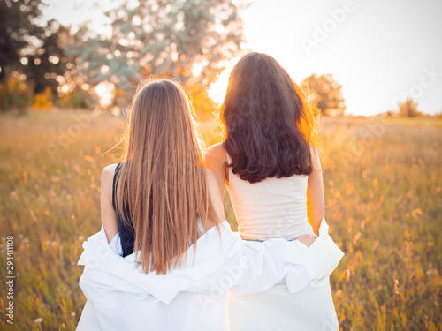 Fotomural  Two girls in white shirts looking on the sunset. Best friends