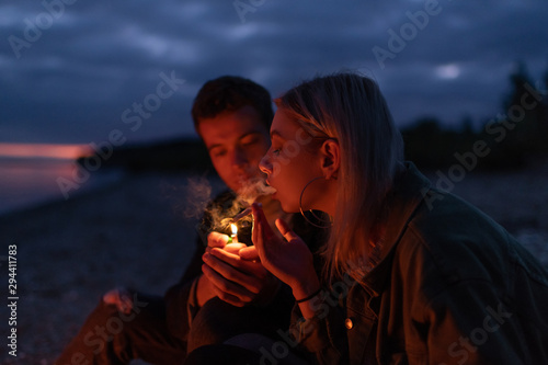 Obraz Couple lighting joint at night in nature - fototapety do salonu