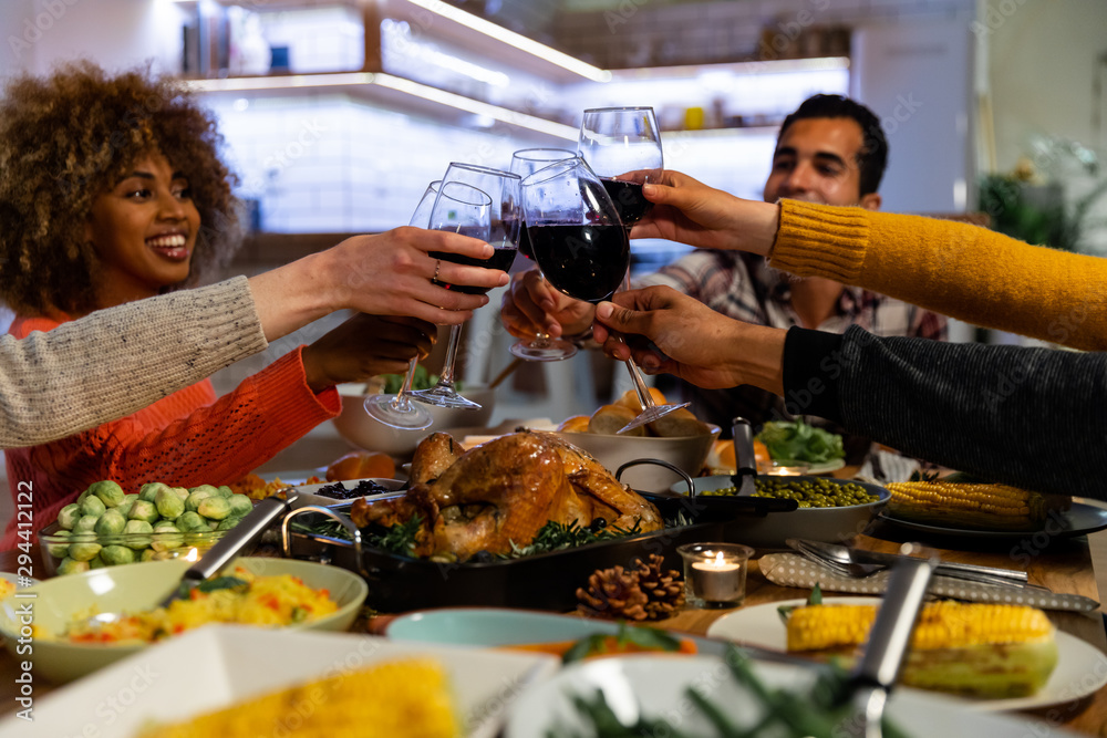 Fototapeta Millennial adult friends celebrating Thanksgiving together at home
