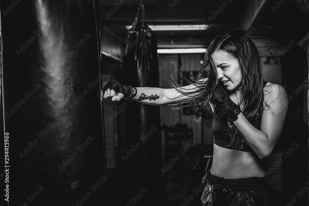 Fototapeta Happy smiling girl has a boxing training at gym with punching bag, black and white photo.