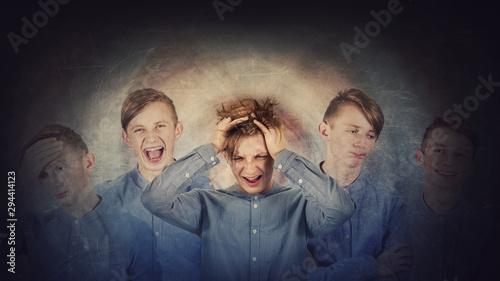 Valokuvatapetti Desperate teenage boy, hands to head, suffer split emotions into different inner personalities
