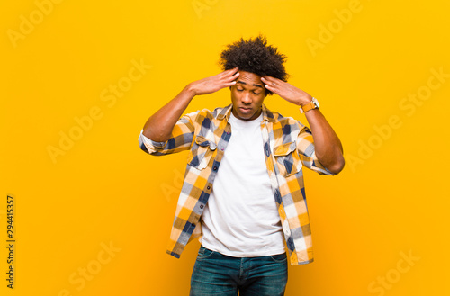 Obraz young black man looking concentrated, thoughtful and inspired, brainstorming and imagining with hands on forehead against orange wall - fototapety do salonu