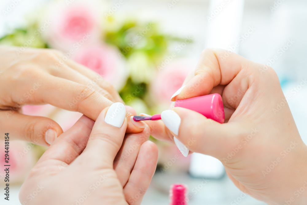 Experienced nail technician applying nail color