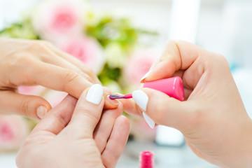 FototapetaExperienced nail technician applying nail color