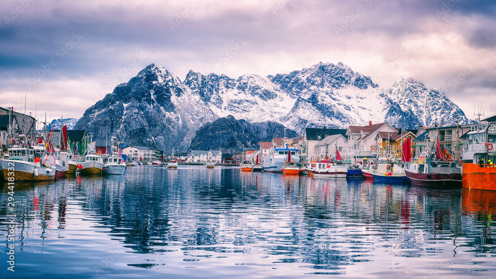 Fototapeta Fishing boats at harbour of cozy small fishing village Henningsvaer in Lofoten Islands, Northern Norway. Amazing landscape with mountains and reflection in the water, travel winter background