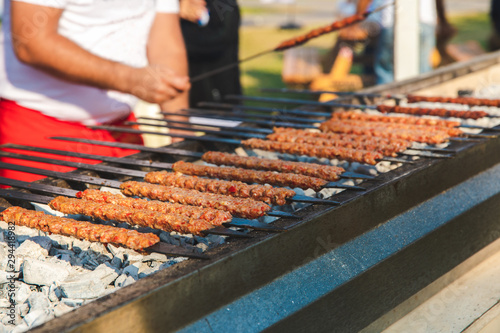 Photo Traditional Turkish Adana Kebab or Kebap on the grill with skewers in the turkish restaurant for dinner
