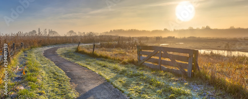 Gate in misty agricultural landscape