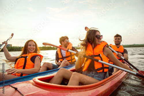 Vászonkép Happy young caucasian group of friends kayaking on river with sunset in the backgrounds