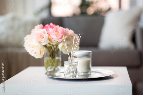 Fotografie, Tablou decoration, hygge and cosiness concept - aroma reed diffuser, candle and flower
