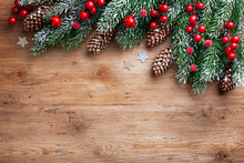 Christmas Background. Snowy Fir Tree Branches With Fir Cones And Red Berries On Wooden Board. Top View With Space For Text.