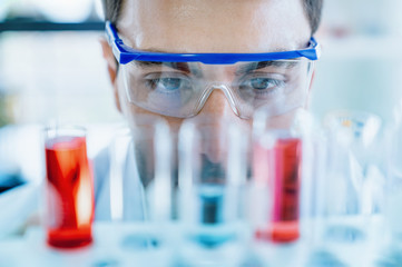 Close up scientist wear protective eye glasses looking at medical test in glass tube while doing research in scientific laboratory
