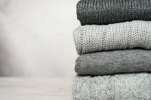 A Stack Of Knitted Winter Sweaters In Several Shades Of Gray On Gray Background