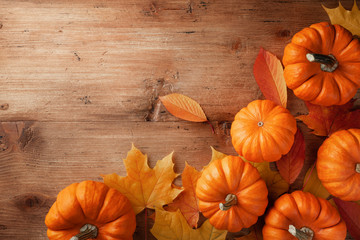 Autumn Thanksgiving background. Pumpkins and maple leaves on wooden table top view.