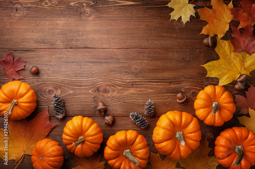 Obraz Autumn Thanksgiving background. Pumpkins, acorns and leaves on rustic wooden table top view. - fototapety do salonu