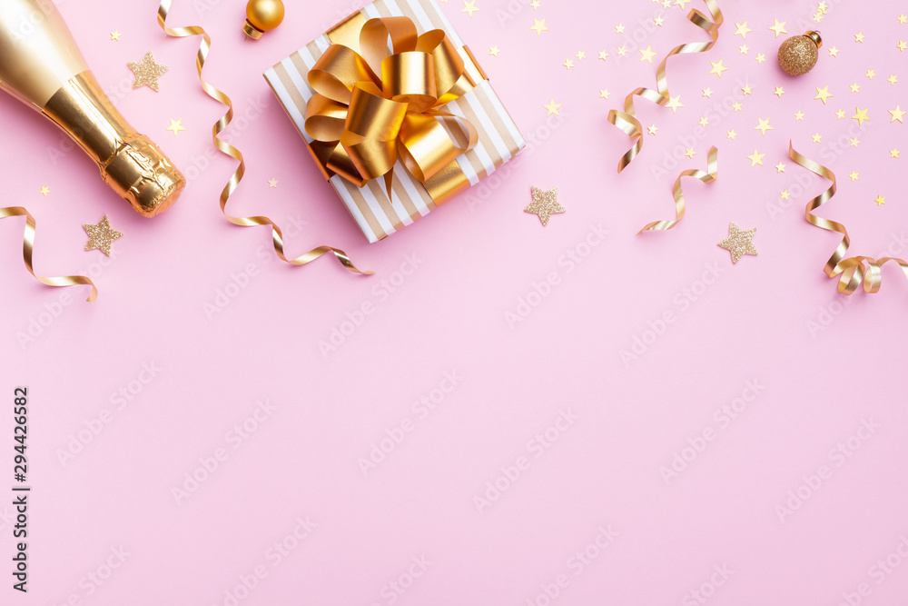 Fototapeta Christmas or New year greeting card. Champagne bottle, gift or present box and golden confetti on pink background top view. Flat lay.