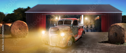 Vintage pickup truck wide open country side with dramatic sunset near the barn