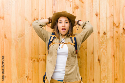 young latin explorer woman against wooden wall background Wallpaper Mural