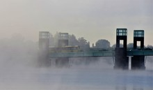 Bus Rides Over The Bridge On The River In The Fog