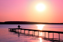 Colorful Sunset Over The Lake With A Pier. A Lone Fisherman Is Fishing On The Pier. Pink And Purple Pastel Watercolor Soft Tones.