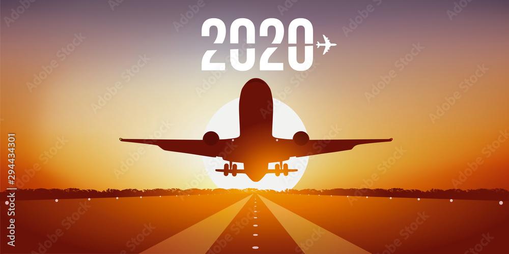 Fototapeta Année 2020 montrant un avion prenant son envol en décollant de la piste d'un aéroport devant un coucher de soleil