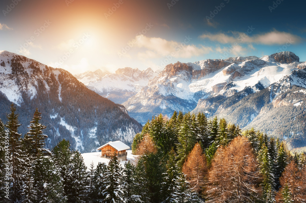 Fototapeta Wooden house in winter mountains at sunset. Ski resort in Dolomite Alps. Val Di Fassa, Italy. Beautiful winter landscape