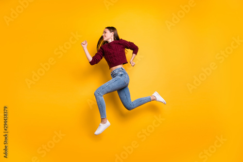 Full body profile side photo of cheerful lady running wearing marsala sweater isolated over yellow - 294438379