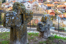 Ancient Stone Crosses At The Churchyard Of St. Petka Eastern Orthodox Church In Tsari Mali Grad Fortress, The Village Of Belchin, Bulgaria In The Background