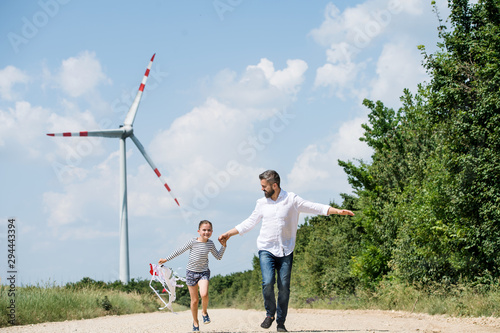 Fototapeta Mature father with small daughter on field on wind farm, running. obraz